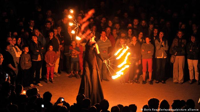 Женщина с факелами танцует на фестивале света в Дармштадте