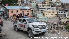 A police car filled with civilians and policemen drives up the Jalousie township where men accused of being involved in the assassination of President Jovenel Moise, have been arrested on July 8, 2021 at the Jalousie township in Haiti. - Police in Haiti have surrounded a group of possible suspects in the assassination of President Jovenel Moise, the UN envoy to Haiti said. Helen La Lime said from the Haitian capital that four members of a group that attacked the presidential palace Wednesday and shot the president have been killed by police and six others are in custody. (Photo by Valerie Baeriswyl / AFP) / The erroneous mention[s] appearing in the metadata of this photo by Valerie Baeriswyl has been modified in AFP systems in the following manner: [A police car filled with civilians and policemen drives up the Jalousie township where men accused of being involved in the assassination of President Jovenel Moise, have been arrested] instead of [Men accused of being involved in the assassination of President Jovenel Moise, are being transported]. Please immediately remove the erroneous mention[s] from all your online services and delete it (them) from your servers. If you have been authorized by AFP to distribute it (them) to third parties, please ensure that the same actions are carried out by them. Failure to promptly comply with these instructions will entail liability on your part for any continued or post notification usage. Therefore we thank you very much for all your attention and prompt action. We are sorry for the inconvenience this notification may cause and remain at your disposal for any further information you may require. (Photo by VALERIE BAERISWYL/AFP via Getty Images)