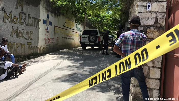 Journalists stand next to a yellow police cordon near the residence of Haiti's slain President Jovenel Moise.