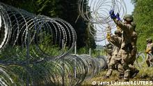 09.07.2021 Lithuanian army soldiers install razor wire on border with Belarus in Druskininkai, Lithuania July 9, 2021. REUTERS/Janis Laizans