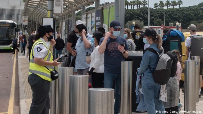 Menschen mit Maske stehen an einem Bus-Terminal