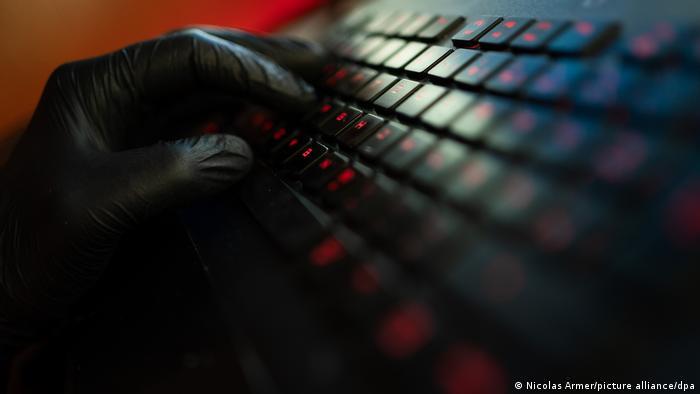 Simbol kibernetičkog napada: ruka u crnoj rukavici na tastaturi