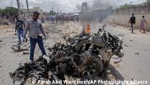 July 10, 2021*** Security forces and civilians gather near the wreckage after a suicide car bomb attack that targeted the city's police commissioner in Mogadishu, Somalia Saturday, July 10, 2021. At least nine people are dead and others wounded after the large explosion, a health official at the Medina hospital said, noting that the toll reflected only the dead and wounded brought there. (AP Photo/Farah Abdi Warsameh)