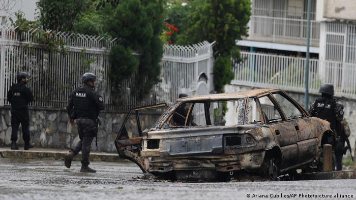 Venezuelan security forces move past a charred vehicle in Caracas