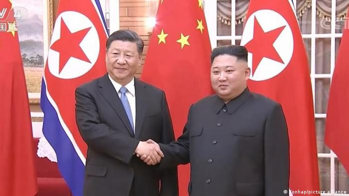Chinese President Xi Jinping (L) shakes hands with North Korean leader Kim Jong-un in 2019.
