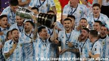 Argentina's Lionel Messi hoists the trophy after beating Brazil 1-0 in the Copa America final soccer match at Maracana stadium in Rio de Janeiro, Brazil, Saturday, July 10, 2021. (AP Photo/Silvia Izquierdo)