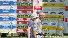 11.07.21 *** People walk past election campaign posters ahead of snap parliamentary election, scheduled on July 11, in Chisinau, Moldova July 7, 2021. REUTERS/Vladislav Culiomza