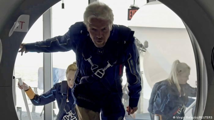 Branson entrando na nave. Atrás dele, há duas mulheres.