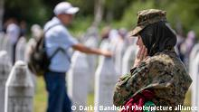 A member of Bosnian armored forces visits the memorial cemetery in Potocari near Srebrenica, Bosnia, Sunday, July 11, 2021. Bosnia is marking the 26th anniversary of the Srebrenica massacre, the only episode of its 1992-95 fratricidal war that has been declared a genocide by international and national courts. The brutal execution of more than 8,000 Muslim Bosniaks by Bosnian Serb troops is being commemorated by a series of events Sunday. (AP Photo/Darko Bandic)