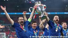 Fußball: EM, Italien - England, Finalrunde, Finale im Wembley Stadion. Italiens Giorgio Chiellini (l) und Leonardo Bonucci tragen die Trophäe und feiern mit ihren Teamkollegen nach dem Sieg . Italien gewinnt das Finale im Elfmeterschießen mit 3:2 und ist Fußball-Europameister. +++ dpa-Bildfunk +++