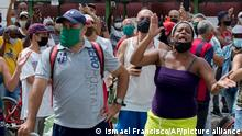 A woman shouts during a an anti-government protest in Havana, Cuba, Sunday, July 11, 2021. Hundreds of demonstrators went out to the streets in several cities in Cuba to protest against ongoing food shortages and high prices of foodstuffs. (AP Photo/Ismael Francisco/A7)