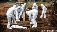 """*** Dieses Bild ist fertig zugeschnitten als Social Media Snack (für Facebook, Twitter, Instagram) im Tableau zu finden: Fach """"Images"""" —> Weltspiegel/Bilder des Tages *** Gravediggers wearing personal protective equipment lower a coffin for burial at a cemetery in Bogor on July 11, 2021, as Indonesia faces its most serious outbreak driven by the highly infectious Delta variant of Covid-19. (Photo by ADITYA AJI / AFP)"""