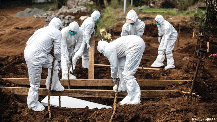 Gravediggers in protective gear lower a COVID-19 victim into the ground in Indonesia