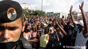 À esquerda, em primeiro plano, está o rosto de um soldado, com boina e máscara cobrindo apenas a boca. Ao fundo, muitas pessoas erquem os braços em protesto.