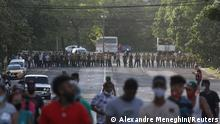 Demonstrators walk away from army soldiers blocking a road during a protest against and in support of the government, amidst the coronavirus disease (COVID-19) outbreak, in Havana, Cuba July 11, 2021. REUTERS/Alexandre Meneghini