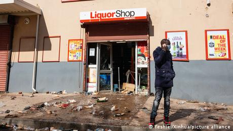 A man stands outside a looted shop in Johannesburg, South Africa (July 11, 2021)