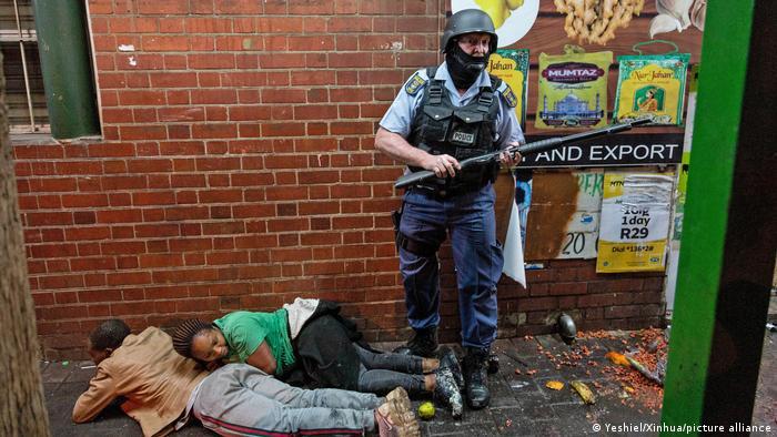 Ein Polizist bewacht in Johannesburg zwei festgenommene Demonstranten