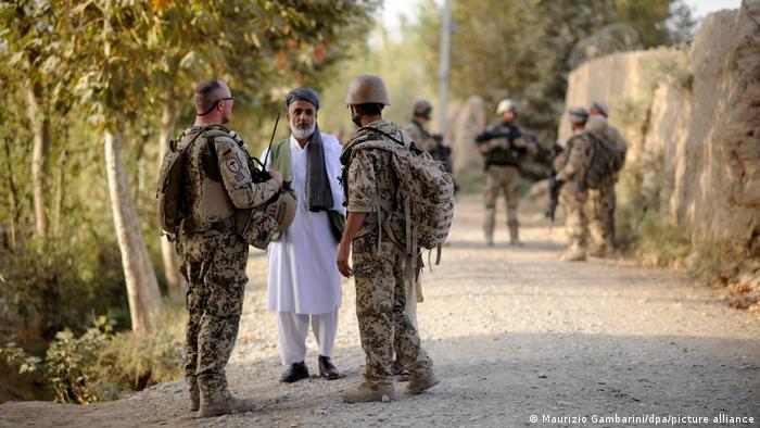 Ein Bundeswehr-Soldat und sein afghanischer Dolmetscher (r.) nahe Kundus im Gespräch mit einem Einwohner (Archivfoto)