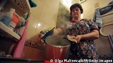 This photo taken on July 7, 2016 shows a woman preparing hot water to wash her hair, in her apartment in Saint Petersburg. For Russians it is a sure sign that summer has really come -- the annual, rolling switch-off of municipal hot water that hits homes across the vast country. From Vladivostok on the Pacific coast to the European exclave Kaliningrad, millions of residents are forced each year to shiver through icy showers as authorities say they have to switch off the system carrying hot water underground, in order to fix ageing pipes. / AFP / Olga MALTSEVA (Photo credit should read OLGA MALTSEVA/AFP via Getty Images)