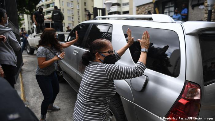 Two women banging on the windows of a government SUV