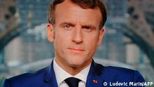 July 12, 2021.*** French President Emmanuel Macron is seen on a TV screen as he speaks during a televised address to the nation from the temporary Grand Palais in Paris on July 12, 2021. - Macron announced mandatory Covid jabs for healthcare staff and that 'Covid pass' will be needed in restaurants from August. (Photo by Ludovic MARIN / AFP)