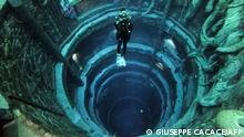 A diver experiences Deep Dive Dubai, the deepest swimming pool in the world reaching 60m, in the United Arab Emirates, on July 10, 2021. - The city of superlatives, with the world's tallest tower among its many records, Dubai now has the deepest swimming pool on the planet complete with a sunken city for divers to explore. (Photo by GIUSEPPE CACACE / AFP)