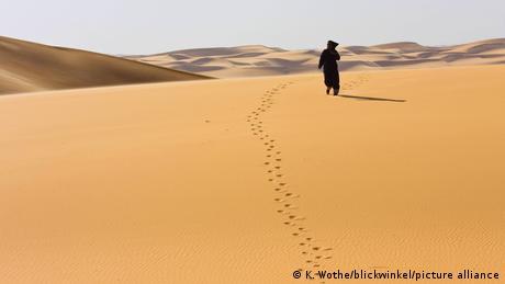 A Bedouin walking across a sand dune in the Sahara Desert