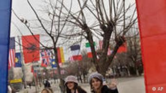 Women walk by Kosovar flag