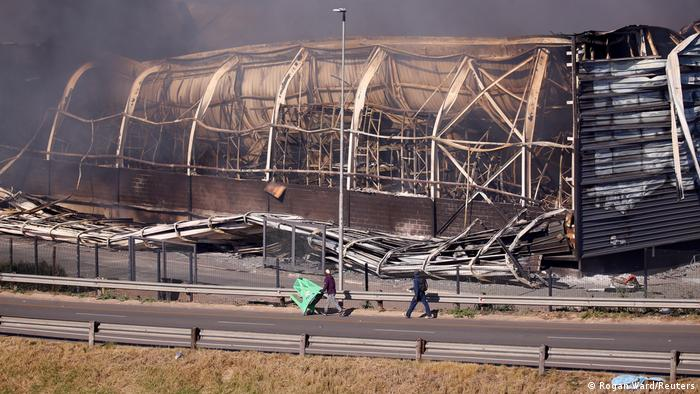 Brookside mall burns next to a road after being looted