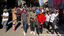 Stick-wielding protesters march through the streets as violence following the jailing of former South African President Jacob Zuma spread to the country's main economic hub in Johannesburg, South Africa, July 11, 2021. REUTERS/ Siphiwe Sibeko