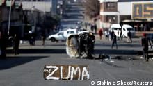 The remains of a burnt car and a sign block the road after stick-wielding protesters marched through the streets, as violence following the jailing of former South African President Jacob Zuma spread to the country's main economic hub in Johannesburg, South Africa, July 11, 2021. REUTERS/Siphiwe Sibeko