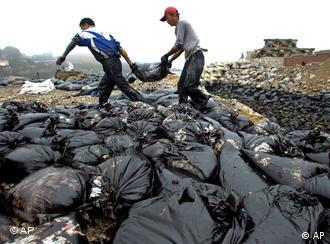 In this photo taken Wednesday, July 21, 2010, workers move a bag on the beach polluted by crude oil after a pipeline explosion in Dalian, in northeast China's Liaoning province. China National Petroleum Corp. said Thursday a vital pipeline has resumed operations after the explosion caused the country's largest reported oil spill. (AP Photo) ** CHINA OUT **