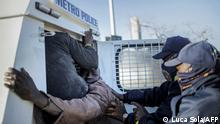 South African Police Service (SAPS) officers detain a suspected looter in Bara Mall, Soweto on July 13, 2021. - Stores in two South African provinces were ransacked for a fifth consecutive day, hours after President Cyril Ramaphosa deployed troops in a bid to quell unrest that has claimed 45 lives. The premier of Gauteng province, which includes Johannesburg, said 10 bodies were found late on July 12 at a looted shopping centre in Soweto, on the city's outskirts. (Photo by LUCA SOLA / AFP)