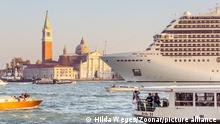 Venice, Italy - October 29, 2016: Big cruise ship with tourists leaving the city of Venice Italy in the evening