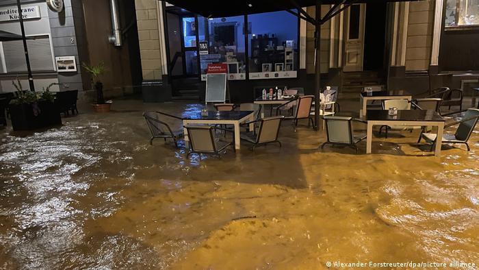 اینجا صحنهای از بالا آمدن سطح آب در کافهای در شهر هاگن واقع در ایالت نوردراین وستفالن است. ماموران آتشنشانی برای کمک به مردم بدون وقفه اقدام به تخلیه آب از زیرزمین خانهها کردهاند. گفته میشود تنها در شهر هاگن، ماموران آتشنشانی در ۲۰۰ ماموریت شرکت کردهاند.
