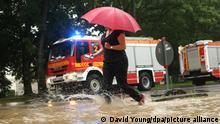 14.07.2021 Eine Frau geht an Feuerwehrfahrzeugen vorbei mit einem Regenschirm über die Morper Allee. +++ dpa-Bildfunk +++