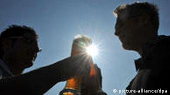 Two people drink beer in the sun