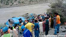 14.07.2021 | Local residents and rescue workers gather at the site of bus accident, in Kohistan Kohistan district of Pakistan's Khyber Pakhtunkhwa province, Wednesday, July 14, 2021. A bus carrying Chinese and Pakistani construction workers on a slippery mountainous road in northwest Pakistan fell into a ravine Wednesday, killing a dozen of people, including Chinese nationals, and dozens were injured, a government official said. (AP Photo)