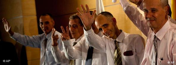 Cuban dissidents wave for press photographers upon arrival at Madrid's Barajas airport from Cuba.