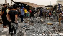 People gather as they inspect the damage at al-Hussain coronavirus hospital where a fire broke out, in Nassiriya, Iraq, July 13, 2021. REUTERS/Khalid al-Mousily