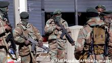 """*** Dieses Bild ist fertig zugeschnitten als Social Media Snack (für Facebook, Twitter, Instagram) im Tableau zu finden: Fach """"Images"""" *** Members of the South African Defence Force (SANDF) gather at the looted Diepkloof Square area in Soweto, Johannesburg on July 13, 2021. - A further 22 people have died during unrest raging in South Africa, a provincial official said on July 13, taking the national death toll from days of violence to 32. President Cyril Ramaphosa on July 12 said the deadly unrest gripping the country is unprecedented in post-apartheid South Africa as he deployed troops to help police crush the violence and looting sparked by the jailing of ex-president Jacob Zuma. (Photo by Phill Magakoe / AFP) (Photo by PHILL MAGAKOE/AFP via Getty Images)"""