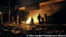 """*** Dieses Bild ist fertig zugeschnitten als Social Media Snack (für Facebook, Twitter, Instagram) im Tableau zu finden: Fach """"Images"""" *** South African Defence Force soldiers keep themselves warm around a fire while stationed in Alexandra Township, near Johannesburg, to assist police in quelling looting and rioting Tuesday, July 13, 2021. South Africa's police say 72 people have been killed and 1,234 have been arrested in unrest set off by the imprisonment last week of former President Jacob Zuma. (AP Photo/Dino Lloyd)"""