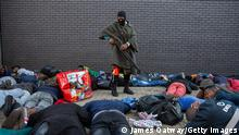 """*** Dieses Bild ist fertig zugeschnitten als Social Media Snack (für Facebook, Twitter, Instagram) im Tableau zu finden: Fach """"Images"""" ***JOHANNESBURG, SOUTH AFRICA - JULY 13: A policeman guards a group of suspected looters who were apprehended at a shopping centre on July 13, 2021 in Vosloorus, Johannesburg, South Africa. South Africa has deployed the military to quell spasms of civil unrest and looting sparked by last week's imprisonment of former president Jacob Zuma. The unrest is also fueled by high unemployment and social and economic fallout from the Covid-19 pandemic, which has hit the country hard. (Photo by James Oatway/Getty Images)"""