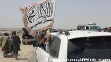 People wave a Taliban flag as they drive through the Pakistani border town of Chaman on July 14, 2021, after the Taliban claimed they had captured the Afghan side of the border crossing of Spin Boldak along the frontier with Pakistan. (Photo by Asghar ACHAKZAI / AFP) (Photo by ASGHAR ACHAKZAI/AFP via Getty Images)