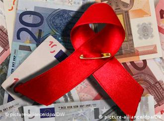 An AIDS ribbon with euro notes in the background
