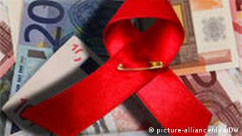 A red AIDS ribbon lies on a pile of banknotes +++(c) dpa - Bildfunk+++