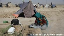 An internally displaced Afghan woman who fled her home due to fighting between the Taliban and Afghan security personnel, burns thorny twigs to make tea in a makeshift tent camp on a rocky patch of land on the edge of the city of Mazar-e-Sharif, northern Afghanistan, Thursday, July 8, 2021. Thousands of people have fled Taliban insurgents sweeping across northern Afghanistan, fearful of their harsh rule. (AP Photo/Rahmat Gul)