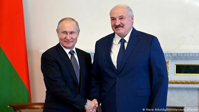 Russian President Vladimir Putin (l) and Belarus President Alexander Lukashenko (r) shake hands in St. Petersburg, Russia