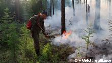 In this handout photo provided by Russian Emergency Ministry Press Service, A firefighter douses a forest fire in Yakutia region, Russia, Wednesday, July 14, 2021. The Russian state agency responsible for fighting forest fires, Avialesookhrana, said Tuesday that more than 300 fires had engulfed 799,500 hectares (more than 1,975,000 acres), and the Sakha-Yakutia region in northeastern Siberia was the worst affected. (Russian Emergency Ministry Press Service via AP)