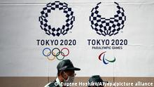 28.06.2021, Japan, Tokio: Beamte der Verkehrssicherheit tragen Mund-Nasen-Bedeckungen als sie an Logos der Olympischen und Paralympischen Spiele 2020 vorbeigehen. In der japanischen Hauptstadt wurden am 28.06 mehr als 310 neue Coronavirus-Fälle bestätigt. Foto: Eugene Hoshiko/AP/dpa +++ dpa-Bildfunk +++